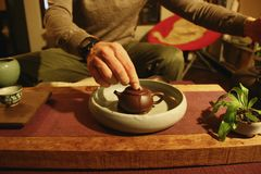 Chinese tea ceremony. A man performs a traditional Chinese tea ceremony with Taiwanese oolong tea, using clay teaware called a yixing pot. The leaves are being Stock Image