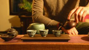Chinese tea ceremony. A man performs a traditional Chinese tea ceremony with Taiwanese oolong tea, using clay teaware called a yixing pot. The leaves are being Stock Photo