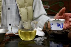 Chinese tea ceremony. A man performs a traditional Chinese tea ceremony with Taiwanese oolong tea, using porcelain teaware called a gaiwan. The leaves are being Stock Photos