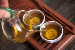 Chinese tea ceremony set. Cropped shot of pouring tea in traditional chinese teaware royalty free stock photo