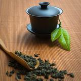 Chinese tea ceremony. Tealeaves and teacup on the bamboo mat Stock Image