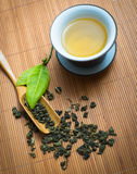 Chinese tea ceremony. Tealeaves and teacup on the bamboo mat Royalty Free Stock Photo