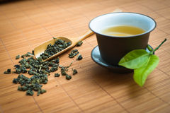 Chinese tea ceremony. Tealeaves and teacup on the bamboo mat Royalty Free Stock Images