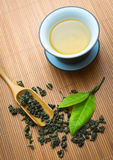 Chinese tea ceremony. Tealeaves and teacup on the bamboo mat Stock Photo