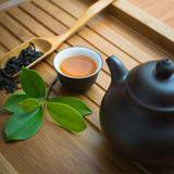 Chinese tea ceremony. Tealeaves,teacup and teapot on the bamboo mat Stock Photos