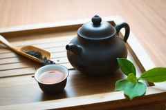 Chinese tea ceremony. Tealeaves,teacup and teapot on the bamboo mat Stock Images