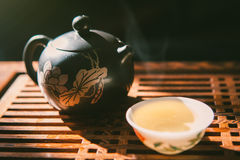 Chinese tea ceremony. Teapot and a cup of green puer tea on wooden tabl with small amount of vapour. Asian traditional culture. Royalty Free Stock Image