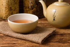 Chinese tea in cup with kettle on right Royalty Free Stock Photo