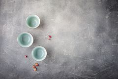 Chinese tea cups on a gray background. Empty Chinese tea cups with a blue pattern and dry buds of roses on a gray background Stock Photos