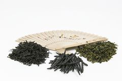 Different kinds of Chinese tea. Chinese tea of different kinds is laid out on a white background. Nearby is the Chinese fan. White background - easy to cut royalty free stock image