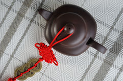 Chinese tea pottery and red decoration. Chinese style tea pottery and traditional red tie decoration, made by featured red tie and aged copper coin, which means Royalty Free Stock Photo