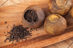 Chinese tea Pu-erh in dried mandarins. Chinese tea Pu-erh packed in dried mandarins on wooden table Royalty Free Stock Photography