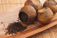 Chinese tea Pu-erh packed in dried mandarins. Chinese dark tea Pu-erh packed in dried mandarins on wooden table Stock Photos