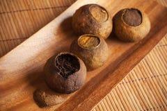 Chinese tea Pu-erh packed in dried mandarins on wooden table. Chinese dark tea Pu-erh packed in dried mandarins peel on wooden table Stock Photos
