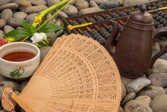 Chinese tea set, abacus, Chinese fan, flowers placed on granite blocks stock photo