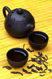 Chinese tea set and wild puerh on yellow mat Royalty Free Stock Images