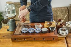 Chinese tea tasting in the tea shop. Tea seller, dressed in European, brews Chinese tea for tasting. Chinese tea set, close-up traditional Chinese teapot and stock images