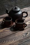 Chinese tea utensils - dark clay teapot and cups, vertical. Top view stock image