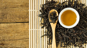 Chinese tea in white ceramic cup and dried tea leaves in wooden spoon Stock Photos