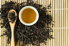 Chinese tea in white ceramic cup and dried tea leaves in wooden spoon Royalty Free Stock Image