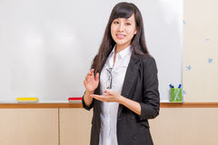 Chinese teacher in front of whiteboard explaining Royalty Free Stock Photos