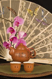 Chinese teapot and antique fan. Chinese teapot and cups filled with tea, antique lace fan with hand painted butterflies and phalaenopsis orchids in background royalty free stock images