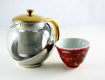 Chinese teapot and cup. Modern Chinese teapot with antique cup, combining several materials: gold,silver and porcelain royalty free stock photography