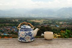 Chinese teapot and cup with green tea on a wooden table on a background of scenic mountains landscape. Pai, Thailand Stock Image