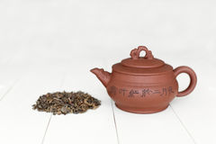 Chinese teapot and pile of green tea Stock Photo