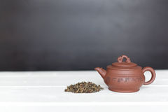 Chinese teapot and pile of green tea Royalty Free Stock Image