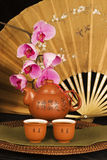 Chinese teapot and silk fan. Chinese teapot and cups filled with tea, antique bronze colored silk fan and phalaenopsis orchids in background royalty free stock photo