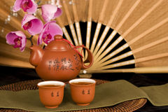 Chinese teapot and silk fan horizontal. Chinese teapot and cups filled with tea, antique bronze colored silk fan and phalaenopsis orchids in background royalty free stock photography