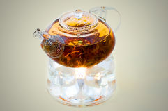 Chinese teapot with tea. On a burning support from glass Stock Images