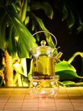 Chinese teapot with tea, on a burning support from glass Royalty Free Stock Image