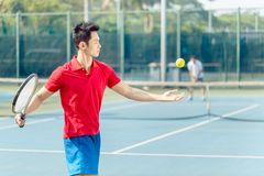 Chinese tennis player ready to hit the ball while serving. Chinese professional tennis player ready to hit the ball with the racket after tossing while serving Stock Photos