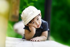 Chinese thinking girl. The Chinese girl with white hat was thinking for something. This photograph was taken in her 26 months Royalty Free Stock Photo