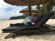 Chinese tourist cover up on a beachchair on the beach royalty free stock images