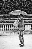 Chinese tourist  with umbrella by  rainy day in tuileries garden Stock Photography