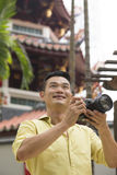 Chinese tourist using his DSLR to take a photo. Royalty Free Stock Photos