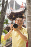 Chinese tourist using his DSLR to take a photo. Stock Photo
