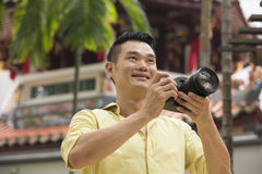 Chinese tourist using his DSLR to take a photo. Royalty Free Stock Image