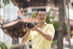 Chinese tourist using his DSLR to take a photo. Royalty Free Stock Photo