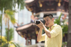 Chinese tourist using his DSLR to take a photo. Stock Photos