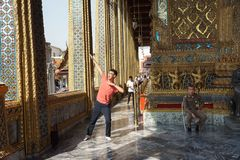 Chinese tourists acts a superhero pose. Bangkok, Thailand - October 15, 2018: Chinese tourists acts a superhero pose for taking a photo in the temple of Emerald royalty free stock photography