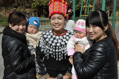 Chinese Tourists Posing with Jingpo Lady, China. Chinese Tourists posing with a lady of the Jingpo ethnic minority in traditional clothes at the Yunnan Royalty Free Stock Image