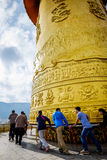 Chinese tourists turn a large golden prayer wheel. Royalty Free Stock Photos