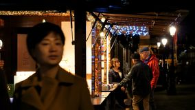 Chinese tourists walking at Strasbourg Christmas Market. STRASBOURG, FRANCE - CIRCA 2018: Chinese tourists walking between Christmas market stalls with souvenirs stock video footage
