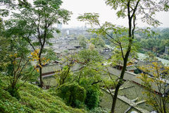 Chinese traditional buildngs at foot of woody mountain in cloudy Stock Images