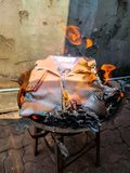 Chinese traditional for burning the fake cloth paper to passed away ancestor`s spirits.  royalty free stock image