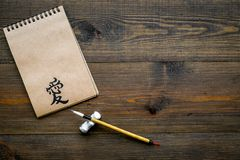 Chinese traditional calligraphy concept. Asian hieroglyph love in craft paper notebook near special writting pen on dark. Wooden background top view royalty free stock photo